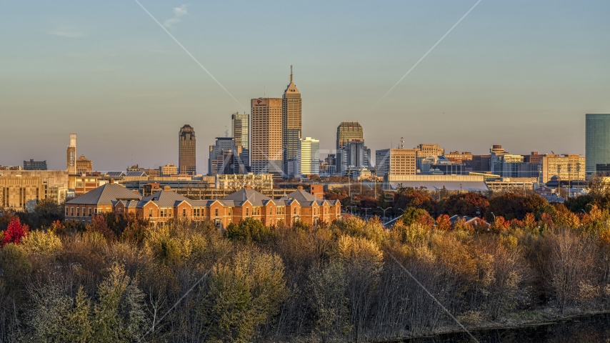The city's skyline at sunset, seen from trees and apartment complex, Downtown Indianapolis, Indiana Aerial Stock Photos | DXP001_092_0009
