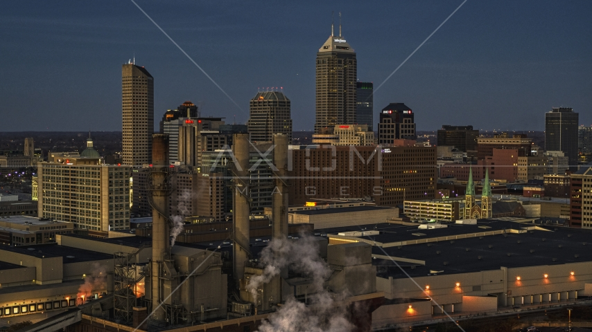 Smoke stacks and a view of city skyline at twilight in Downtown Indianapolis, Indiana Aerial Stock Photos | DXP001_093_0001