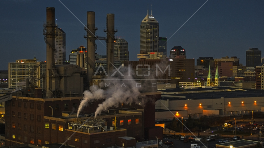 Factory smoke stacks with view of the city skyline at twilight, Downtown Indianapolis, Indiana Aerial Stock Photos | DXP001_093_0003