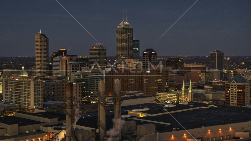 Giant skyscrapers of the city skyline at twilight, seen from smoke stacks, Downtown Indianapolis, Indiana Aerial Stock Photos | DXP001_093_0005