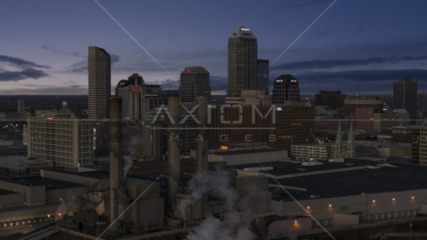Smoke stacks and a view of city skyline at twilight in Downtown Indianapolis, Indiana Aerial Stock Photos | DXP001_093_001
