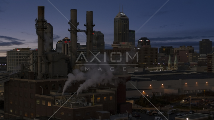 Factory smoke stacks with city skyline in the background at twilight, Downtown Indianapolis, Indiana Aerial Stock Photos | DXP001_093_003