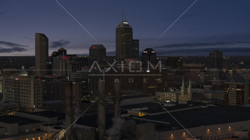 Giant skyscrapers of the city skyline at twilight, seen from smoke stacks, Downtown Indianapolis, Indiana Aerial Stock Photos | DXP001_093_005