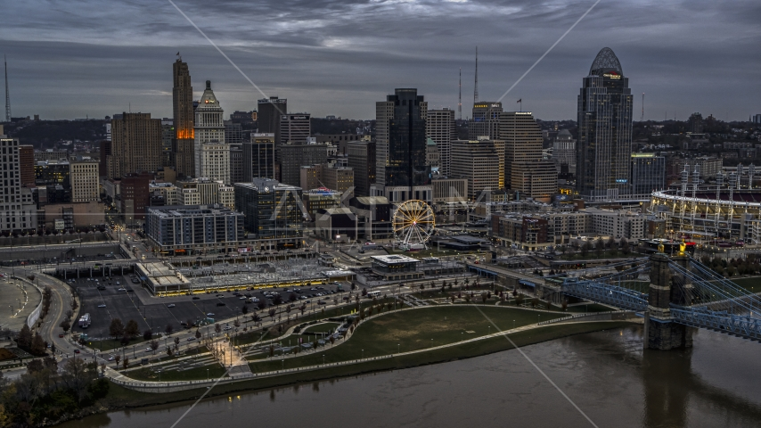 The city's downtown skyline and Ferris wheel at sunset from Ohio River, Downtown Cincinnati, Ohio Aerial Stock Photos | DXP001_097_0011