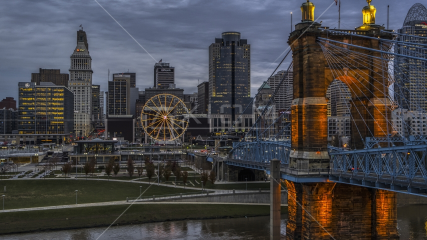 The Roebling Bridge near the Ferris wheel and city skyline at sunset, Downtown Cincinnati, Ohio Aerial Stock Photos DXP001_097_0014