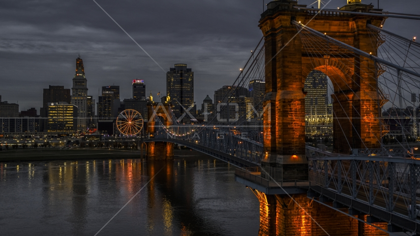 The city skyline behind Roebling Bridge lit up at twilight, seen from Ohio River, Downtown Cincinnati, Ohio Aerial Stock Photo DXP001_098_0003 | Axiom Images