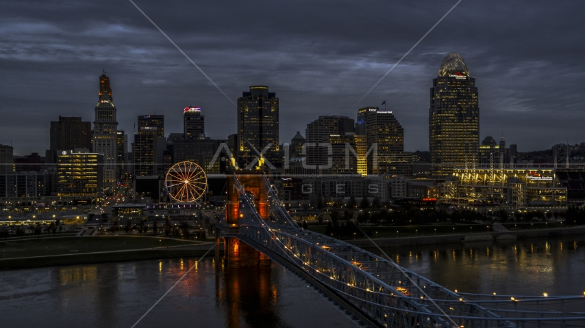 The Roebling Bridge lit up at twilight by the city skyline, Downtown Cincinnati, Ohio Aerial Stock Photos | DXP001_098_0004