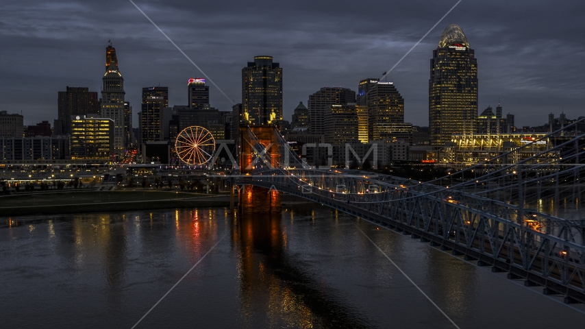 The lights of city skyline and bridge at twilight seen from the river, Downtown Cincinnati, Ohio Aerial Stock Photos | DXP001_098_0007