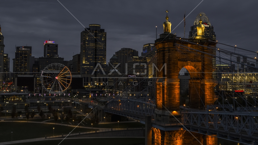 City skyline, Ferris wheel and Roebling Bridge lit up at twilight, Downtown Cincinnati, Ohio Aerial Stock Photos | DXP001_098_0008