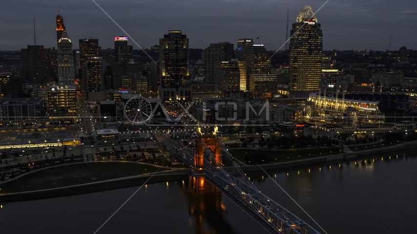 A view of the lights of city skyline and bridge at twilight, seen from river, Downtown Cincinnati, Ohio Aerial Stock Photos | DXP001_098_0009