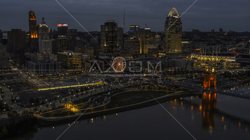 The lights of city's downtown skyline and bridge at twilight, seen from the river, Downtown Cincinnati, Ohio Aerial Stock Photos | DXP001_098_0010