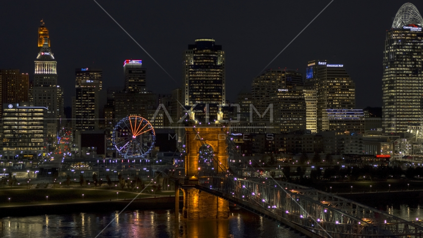 The Ferris wheel by Roebling Bridge at night, with city skyline in background, Downtown Cincinnati, Ohio Aerial Stock Photos | DXP001_098_0023