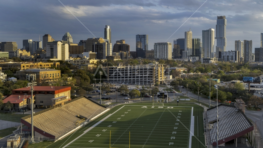 A view of skyscrapers and office buildings at sunset in Downtown Austin, Texas, seen from football stadium Aerial Stock Photos | DXP002_105_0002