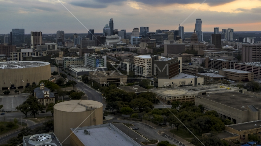 A hospital with skyscrapers in the background at sunset in Downtown Austin, Texas Aerial Stock Photos   DXP002_105_0006