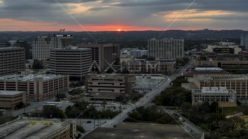 A view of distant, setting sun behind the university campus, Austin, Texas Aerial Stock Photo DXP002_105_0016 | Axiom Images