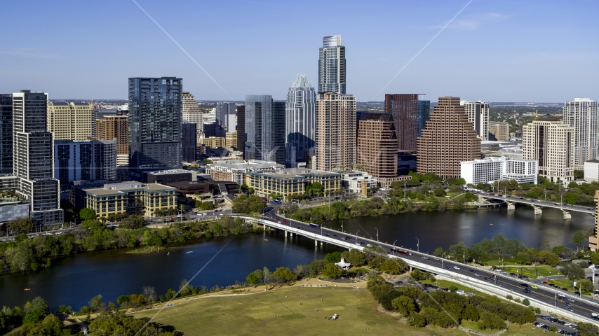 The city's skyline on the other side of Lady Bird Lake, seen from park by bridge, Downtown Austin, Texas Aerial Stock Photo DXP002_109_0004 | Axiom Images