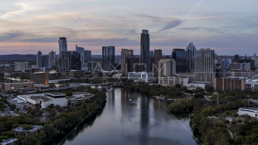 A view of of The Austonian and city skyline seen from Lady Bird Lake at twilight in Downtown Austin, Texas Aerial Stock Photos | DXP002_110_0009