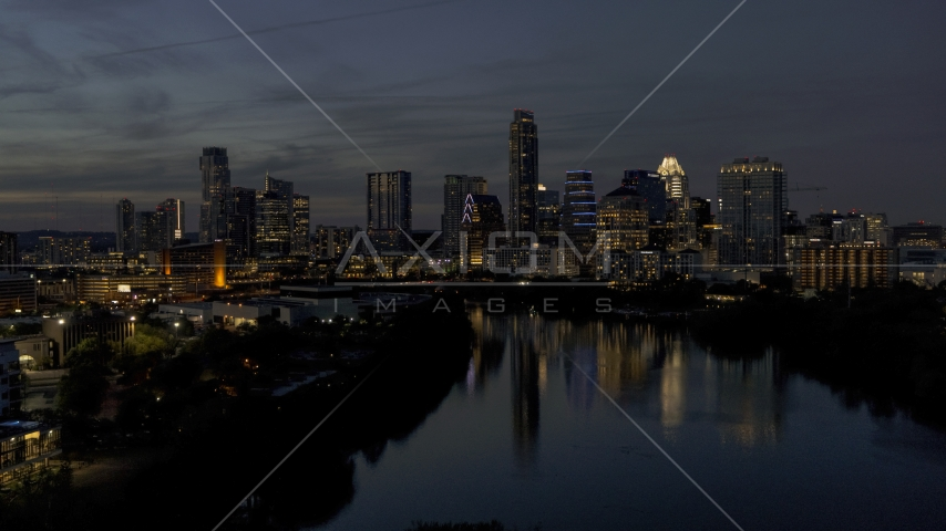 A view of Lady Bird Lake, focus on the waterfront skyline at twilight in Downtown Austin, Texas Aerial Stock Photos | DXP002_111_0001