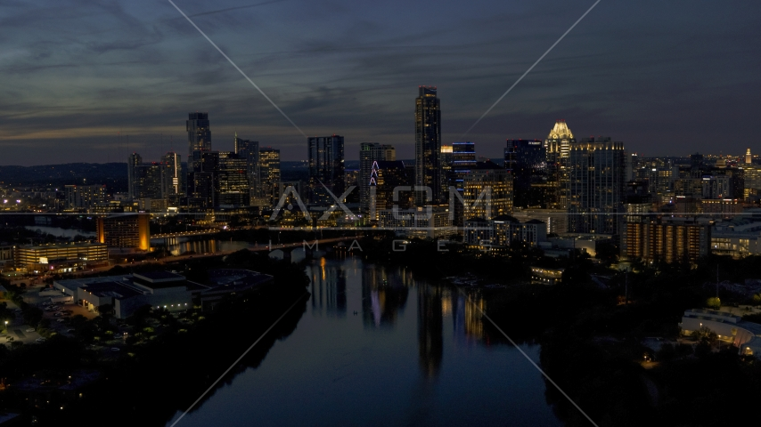 A view of Lady Bird Lake, focus on the waterfront skyline at twilight in Downtown Austin, Texas Aerial Stock Photos | DXP002_111_0002