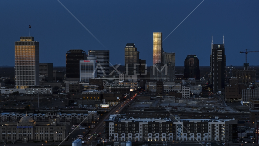 Towering skyscrapers reflecting light in the city skyline at twilight before descent, Downtown Nashville, Tennessee Aerial Stock Photos | DXP002_115_0008