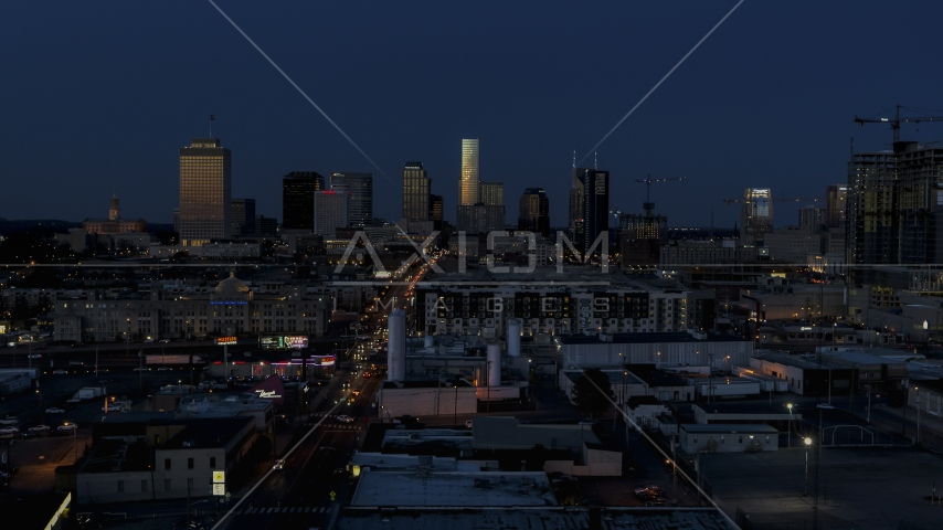 A wide view of skyscrapers reflecting light in the city skyline at twilight in Downtown Nashville, Tennessee Aerial Stock Photos | DXP002_115_0009