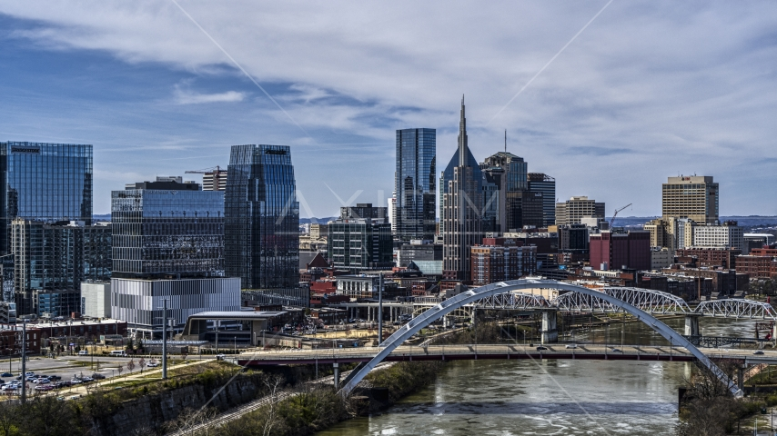Office high-rise and skyscrapers seen from river and bridge in Downtown Nashville, Tennessee Aerial Stock Photos | DXP002_116_0010