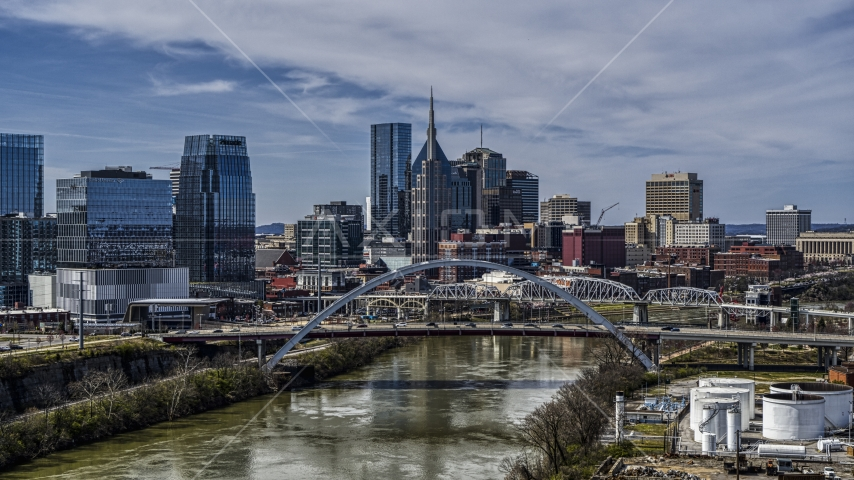 A bridge and the river while focused on city skyscrapers in Downtown Nashville, Tennessee Aerial Stock Photos | DXP002_116_0015