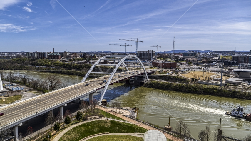 A barge sailing away from a bridge in Nashville, Tennessee Aerial Stock Photos | DXP002_117_0003