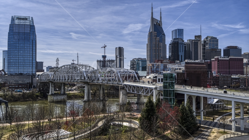 A pedestrian bridge with view of Broadway across the Cumberland River, Downtown Nashville, Tennessee Aerial Stock Photos | DXP002_117_0008