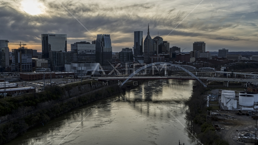 The city skyline behind a bridge on Cumberland River at sunset, Downtown Nashville, Tennessee Aerial Stock Photos | DXP002_119_0009