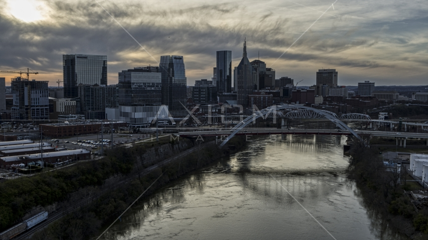 The city skyline behind a bridge on Cumberland River at sunset, Downtown Nashville, Tennessee Aerial Stock Photos | DXP002_119_0010