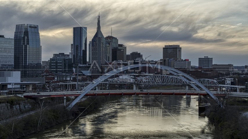 A view of riverfront skyline near a bridge and the Cumberland River at sunset, Downtown Nashville, Tennessee Aerial Stock Photos | DXP002_120_0004