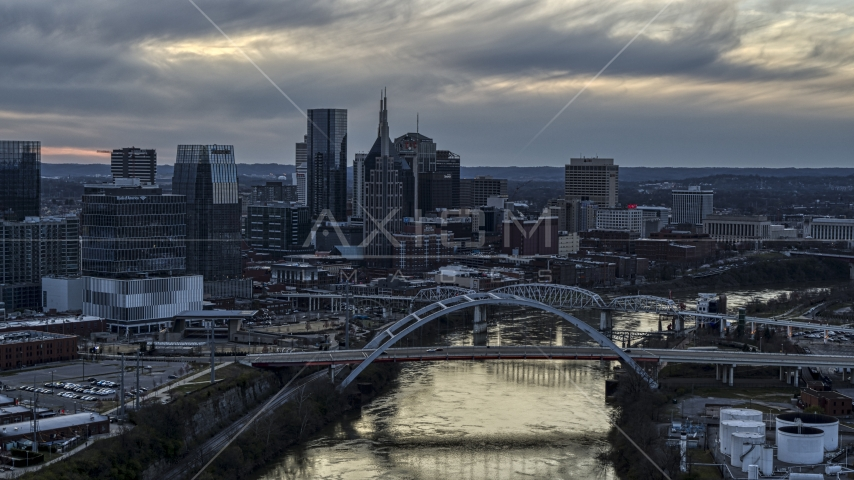 A view of the riverfront skyline and bridges spanning the Cumberland River at sunset, Downtown Nashville, Tennessee Aerial Stock Photos | DXP002_120_0008