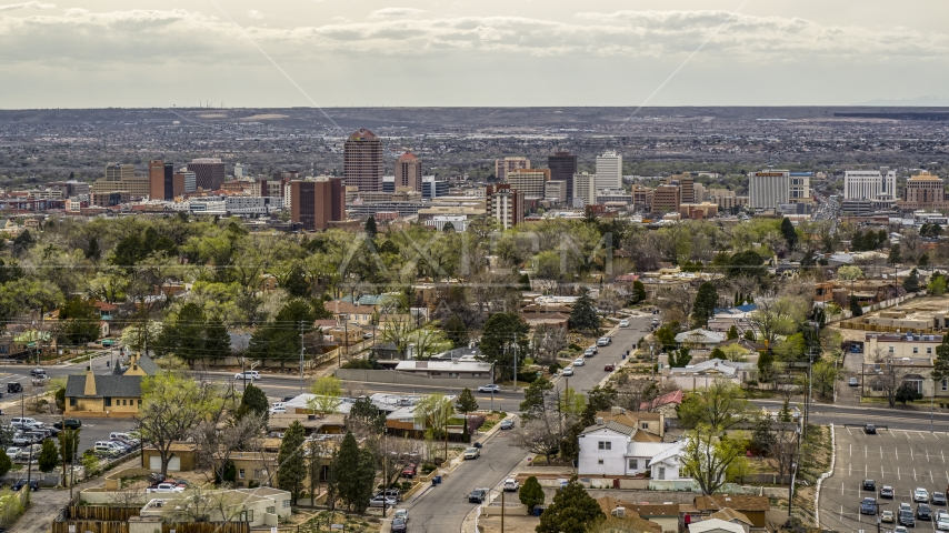 Wide view of city's high-rises seen while flying by homes, Downtown Albuquerque, New Mexico Aerial Stock Photo DXP002_126_0005 | Axiom Images