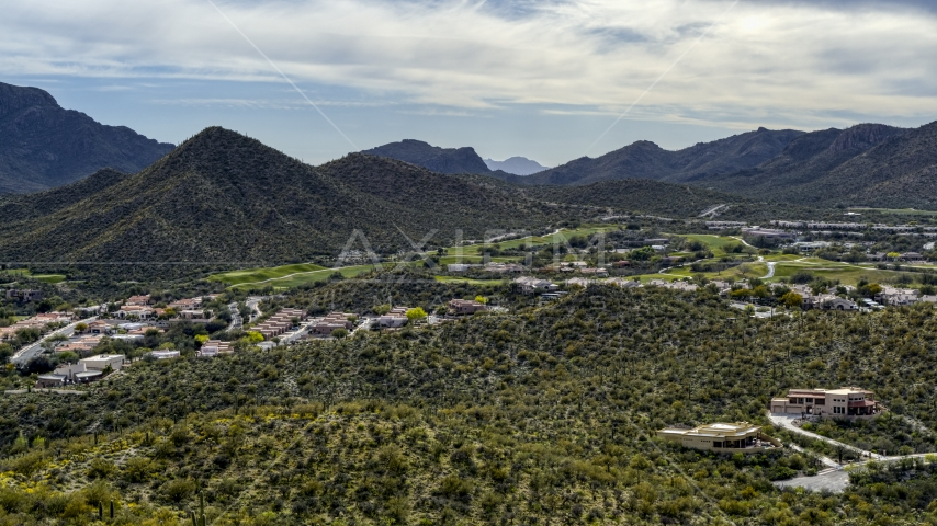 A view of homes and golf course near a mountain peak in Tucson, Arizona Aerial Stock Photos | DXP002_145_0001