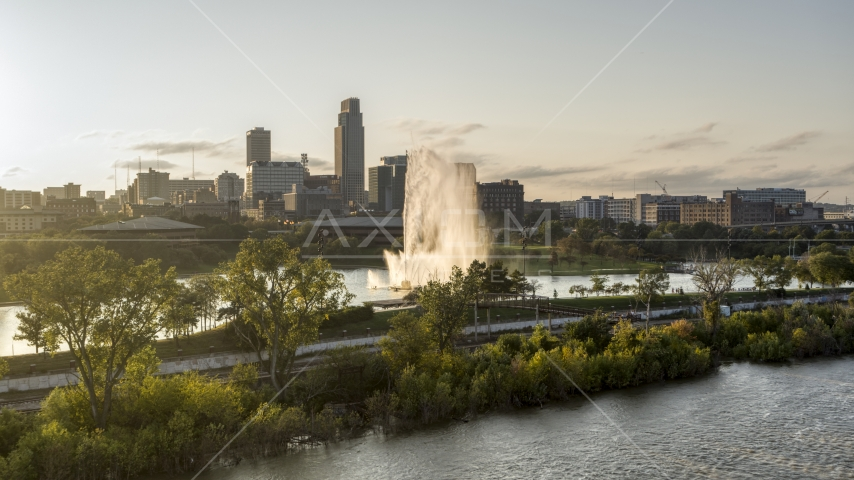 A fountain and riverfront park with view of skyline at sunset, Downtown Omaha, Nebraska Aerial Stock Photo DXP002_172_0003 | Axiom Images
