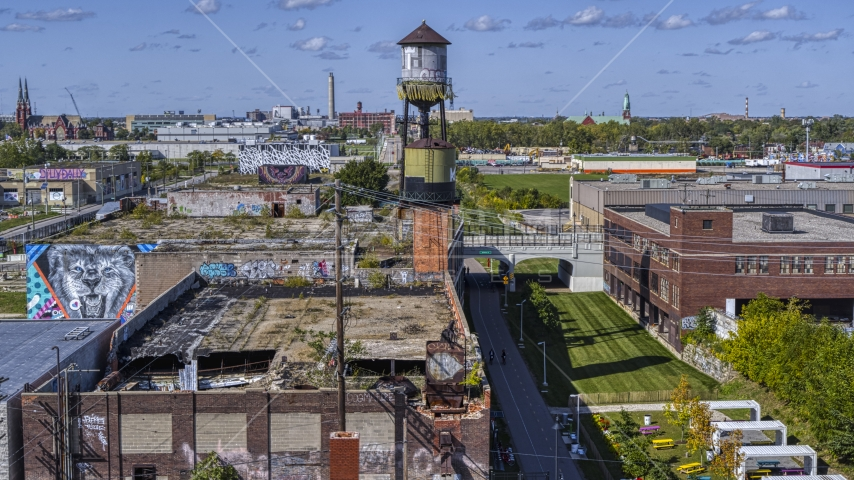 A water tower atop an abandoned brick building in Detroit, Michigan Aerial Stock Photos | DXP002_194_0013