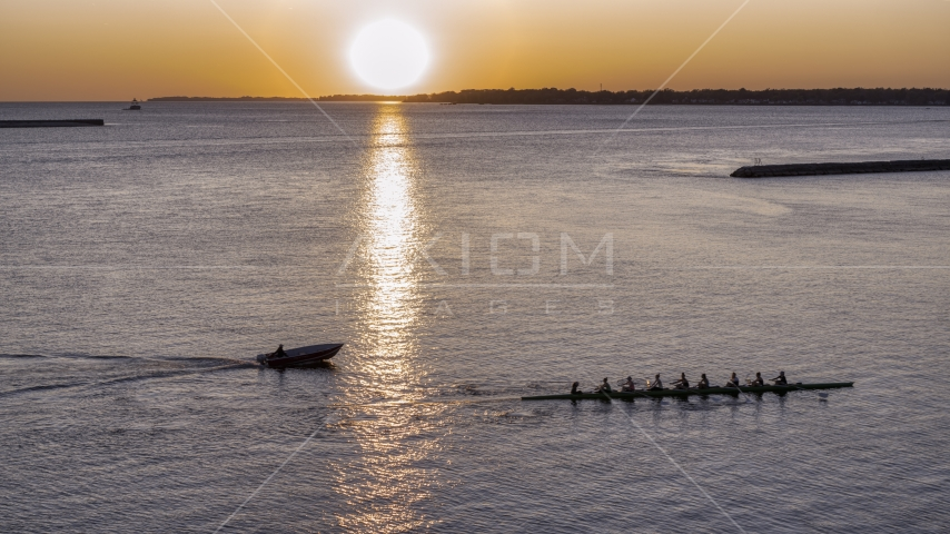 A view of Lake Erie as a rowboat and speedboat pass at sunset, Buffalo, New York Aerial Stock Photo DXP002_204_0005 | Axiom Images