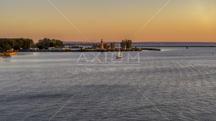 A sailboat on Lake Erie near lighthouse at sunset, Buffalo, New York Aerial Stock Photo DXP002_204_0007 | Axiom Images