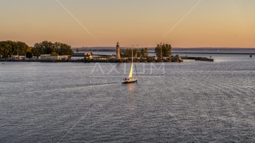 A sailboat on Lake Erie near a lighthouse at sunset, Buffalo, New York Aerial Stock Photo DXP002_204_0008 | Axiom Images