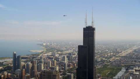 AX0001_043.0000282F - Aerial stock photo of The top of the Willis Tower and a helicopter on a hazy day, Chicago, Illinois