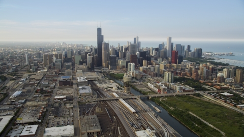 AX0001_076.0000284F - Aerial stock photo of Train yards by the Chicago River near the downtown skyline on a hazy day, Downtown Chicago, Illinois
