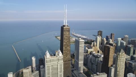 AX0001_087.0000290F - Aerial stock photo of The John Hancock Center skyscraper with Navy Pier in the background, Downtown Chicago, Illinois