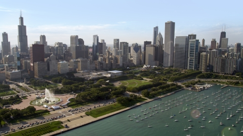 AX0002_005.0000214F - Aerial stock photo of Grant Park and Downtown Chicago skyscrapers near boats in the harbor, Illinois