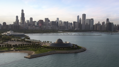 AX0002_086.0000203F - Aerial stock photo of The Adler Planetarium and Astronomy Museum with the Downtown Chicago skyline and harbor in background, Illinois