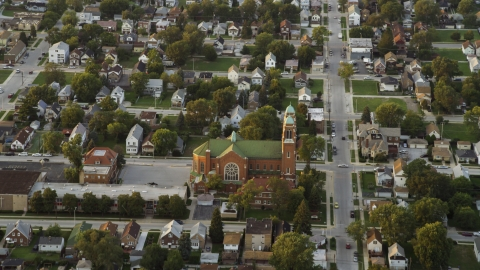 AX0003_006.0000217F - Aerial stock photo of A church in a suburban neighborhood at sunset, Calumet City, Illinois