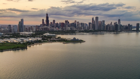 AX0003_029.0000000F - Aerial stock photo of Downtown Chicago skyline and the Adler Planetarium seen from Lake Michigan, at sunset, Illinois