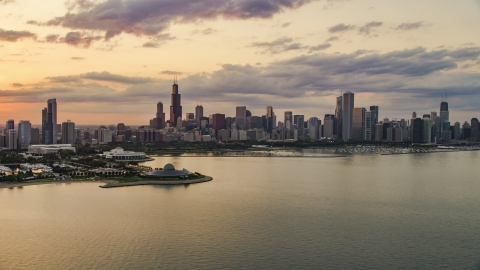 AX0003_029.0000188F - Aerial stock photo of A view of Downtown Chicago skyline and the Adler Planetarium seen from Lake Michigan, at sunset, Illinois