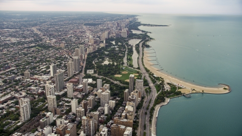 AX0003_053.0000251F - Aerial stock photo of Lake Shore Drive by apartment buildings and Lincoln Park on a cloudy day at sunset, North Chicago, Illinois