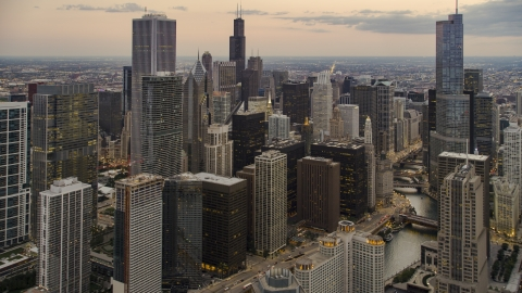 AX0003_079.0000288F - Aerial stock photo of Skyscrapers and high-rises by Chicago River at twilight in Downtown Chicago, Illinois